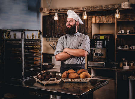 Bearded chef in uniform showing tray of fresh bread in the kitchen of the bakery.