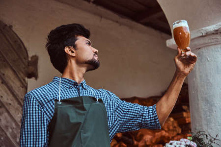 Expert brewer in apron standing outdoors checking the quality of brewed drink at brewery factory.