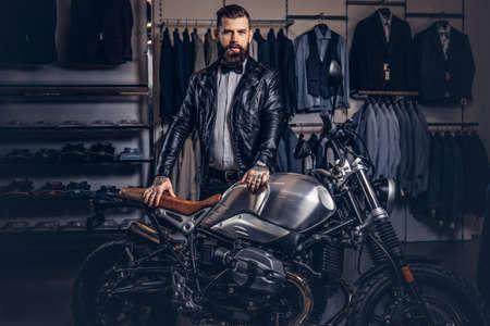 Hombre barbudo tatuado con estilo vestido con chaqueta de cuero negro y pajarita posando junto a una moto deportiva retro en una tienda de ropa para hombre.