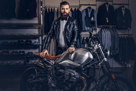 Stylish tattooed bearded man with dressed in black leather jacket and bow tie posing near retro sports motorbike at mens clothing store.