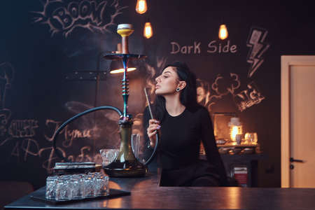 Hot brunette girl in seductive black clothes smokes a hookah while sitting on the counter in a nightclub. Stock Photo