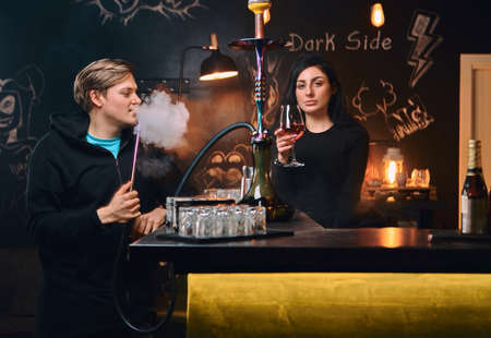 Handsome guy in hoodie smokes a hookah and seductive brunette woman drinks wine at nightclub or bar. Stock Photo