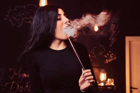 Close-up photo of a seductive brunette girl in black top smokes a hookah in nightclub or hookah bar.