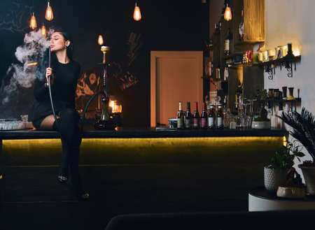 Sexy brunette girl in seductive black clothes smokes a hookah while sitting on counter in a nightclub or bar. Stock Photo