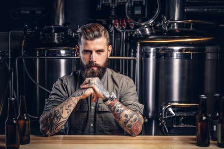 Porträt eines nachdenklichen tätowierten Hipster-Mannes mit stylischem Bart und Haaren im Hemd in der Indie-Brauerei.