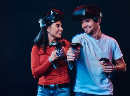 Happy couple of gamers with controllers and VR headsets.