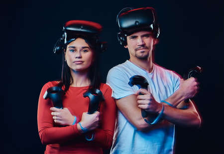 Young caucasian couple with VR headsets and controllers.