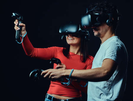 Happy friends playing video games wearing virtual reality glasses with controllers. Reklamní fotografie