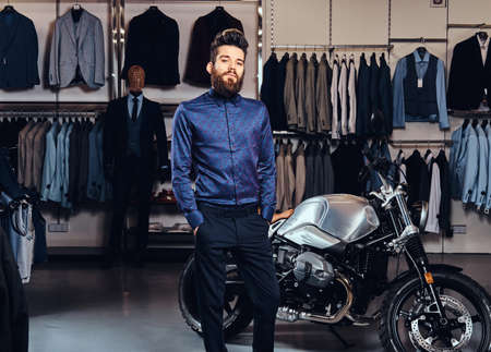 Fashionable man with full beard trendy dressed posing near retro sports motorbike at the mens clothing store. Foto de archivo
