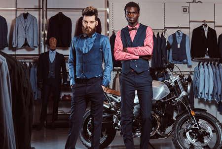 Dos hombres elegantes elegantemente vestidos de pie junto a motos deportivas retro en la tienda de ropa para hombres.