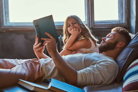 Handsome young father reading storybook his little daughter on bed. 写真素材