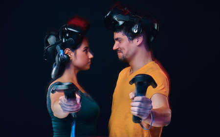 Happy young couple of gamers posing with virtual reality goggles and controllers. 스톡 콘텐츠