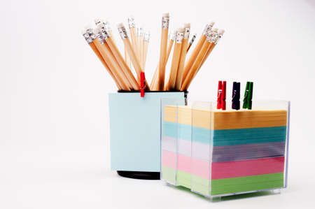 Group of pencils and note papers, isolated on a white background.