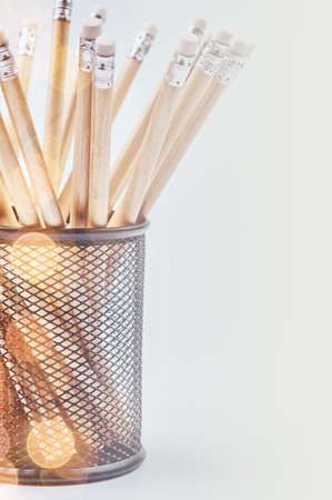 Group of pencils in a black basket, isolated on a gray background. Imagens