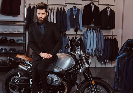 Bearded stylish man dressed in black suit leaning on a retro sports motorbike at the mens clothing store.