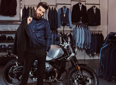 Hombre elegantemente vestido sostiene chaqueta posando junto a motos deportivas retro en la tienda de ropa para hombres.