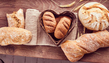 Hot freshly buns in a heart-shaped basket. 免版税图像