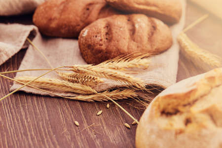 Delicious freshly bakery products and spikelets of wheat on wooden background.