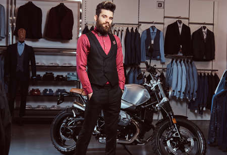 Elegantly dressed man posing with hands in pockets near retro sports motorbike at the mens clothing store.