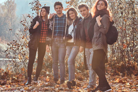 Group of young friends hugging together and lookina at camera in beautiful autumn forest.