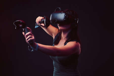 Beautiful young woman with virtual reality headset and joysticks playing video games. 版權商用圖片