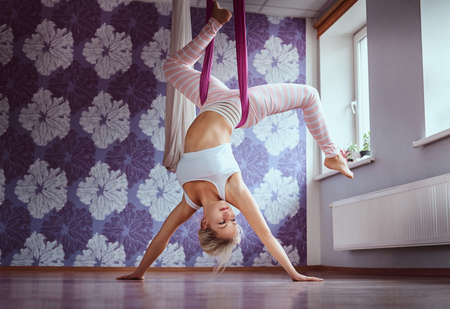 Young woman doing aerial yoga practice in purple hammock in fitness club. 免版税图像