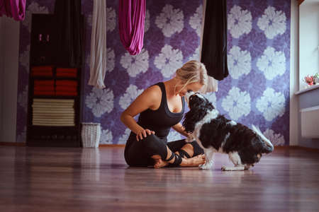 Attractive woman playing with her cute dog while sitting on floor in yoga fitness club. 版權商用圖片
