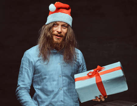 Happy male with long hair and beard in blue shirt and red Santa hat holds gift box.