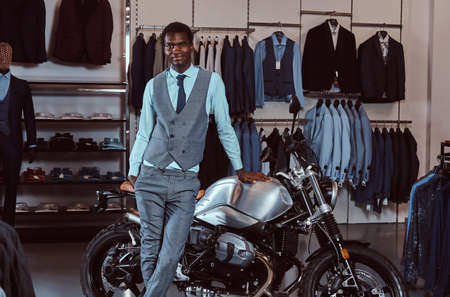 Elegantly dressed African American young man posing near retro sports motorbike at the mens clothing store.