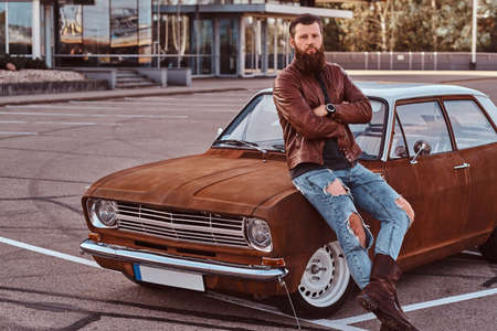 Bearded male dressed in brown leather jacket and boots leaning on tuned retro car in the city parking near skyscraper.