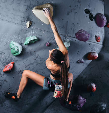 Back view of a professional sports climber woman training on wall indoor.
