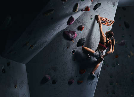 Young woman in shorts and sports bra exercising on a bouldering wall indoors. Archivio Fotografico
