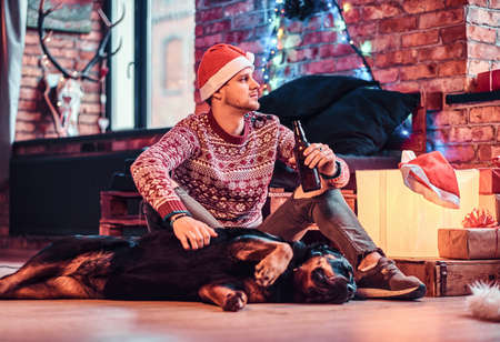 A stylish man holding a bottle with beer while sitting with his cute dog in a decorated living room at Christmas time.