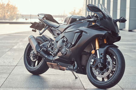 Close-up photo of a black superbike outside near building.