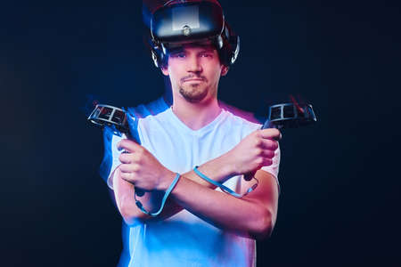 Pro gamer with bristle dressed in white shirt wearing virtual reality glasses and holds joysticks, posing with crossed arms.