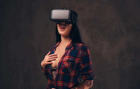 Tattooed girl wearing a red unbuttoned checked shirt wearing a VR headset. Stock Photo