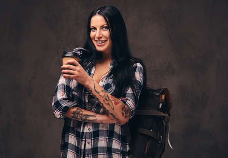 Smiling tattooed girl backpack holding a takeaway coffee in a studio.