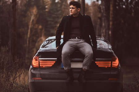 A stylish young man wearing a black coat sitting on the trunk of a car in the autumn forest