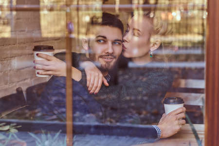 Beautiful girl sitting on her boyfriends lap on the cafe behind the window.