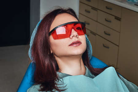 Close-up photo of a woman wearing protective glasses sitting in a dental chair in the clinic.