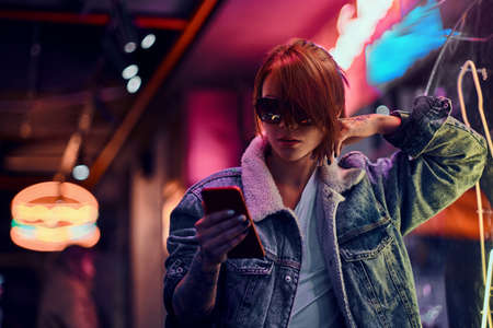 Stylish redhead girl using a phone while leaning on the illuminated signboard in the night on the street.