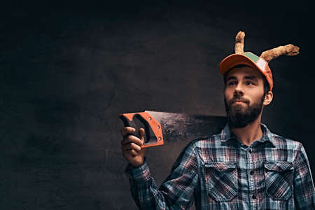 Christmas concept. Worker, carpenter, handyman is posing with a saw.