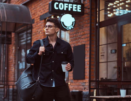 A young handsome man holding a takeaway coffee while standing near a cafe outdoors.