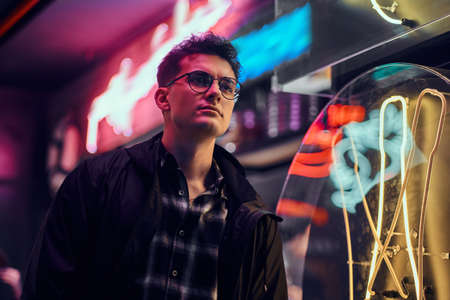 A handsome young man standing at night in the street. Illuminated signboards, neon, lights.