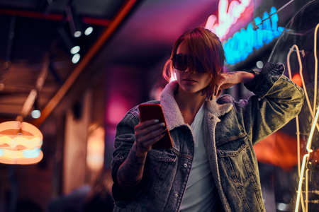 Stylish redhead girl using a phone while leaning on the illuminated signboard in the night on the street. 版權商用圖片 - 112991981