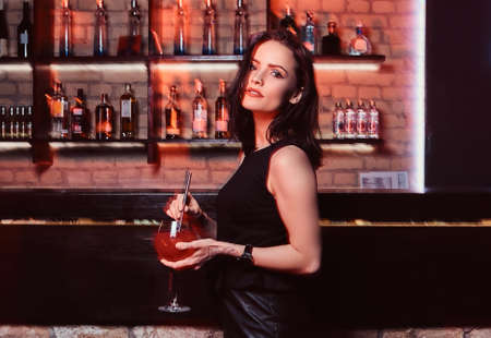 A beautiful girl wearing elegant clothes holding a cocktail while standing next to the bar counter Stok Fotoğraf