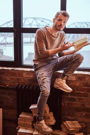 A young handsome student with stylish beard and hair holding a book and looking at camera Stock Photo