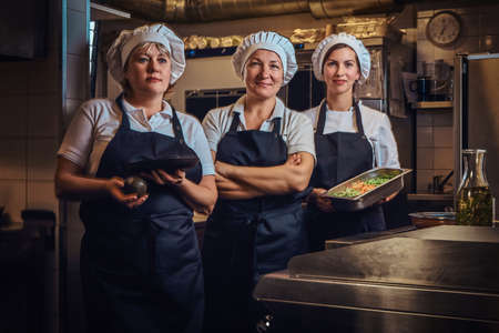 Cooking team wearing a uniform holding containers with chopped vegetables, posing for a camera at restaurants kitchen.