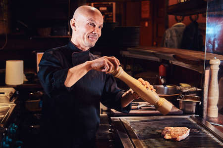 Master chef cooking delicious beef steak on a kitchen in a restaurant, pepper the meat with a pepper mill.