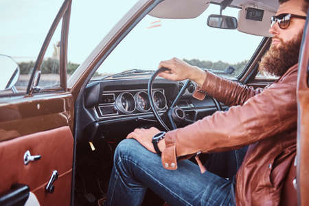 Bearded male in sunglasses dressed in brown leather jacket sits behind the wheel of a tuned retro car with open door.